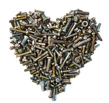 A Heart Shaped Figure Laid Out From Various Assorted Rusty Metal Old Bolts, Screws, Nails, Nuts. The Concept Of Metallic Artificial Heart Machine, Robot, Mechanism. The Concept Of Valentine's Day.