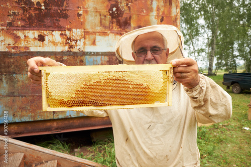 old asian beekeeper. Senior apiarist presenting honey comb Canvas Print