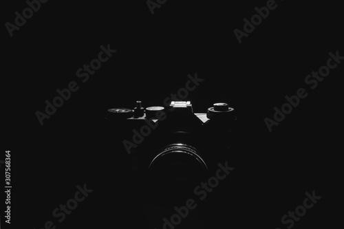 Old black film camera on black background under spot light. Canvas Print