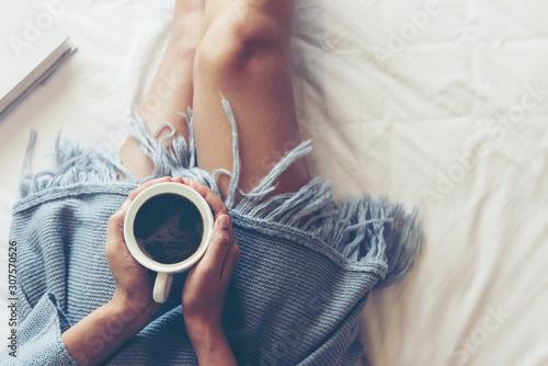 Zamyka w górę nóg kobiet na białym łóżku w sypialni. Kobiety czytające książkę i pijące kawę rano relaksują nastrój w sezonie zimowym. Koncepcja stylu życia.