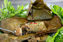 Steamed Fish With Curry Paste In Banana Leaf Wrapped In White Dish Thai Food (Thai Language Call Hor Mok) On Gray Table