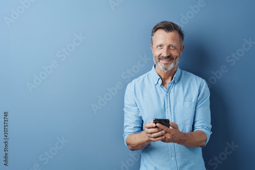Fototapeta  Happy relaxed man holding his mobile phone