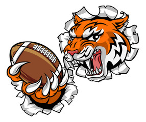 A tiger American Football player cartoon animal sports mascot holding a ball in its claw