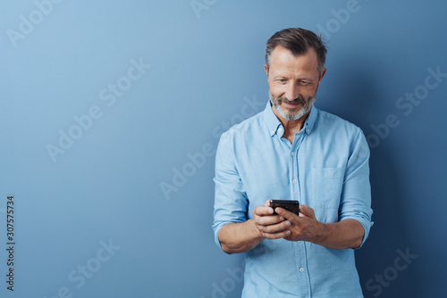 Middle-aged man reading an sms on his mobile Wallpaper Mural