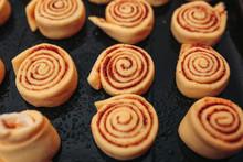 Unbaked Cinnamon Rolls On The Black Baking Pan On The Orange Background. Macro Unbaked Cinnamon Rolls.