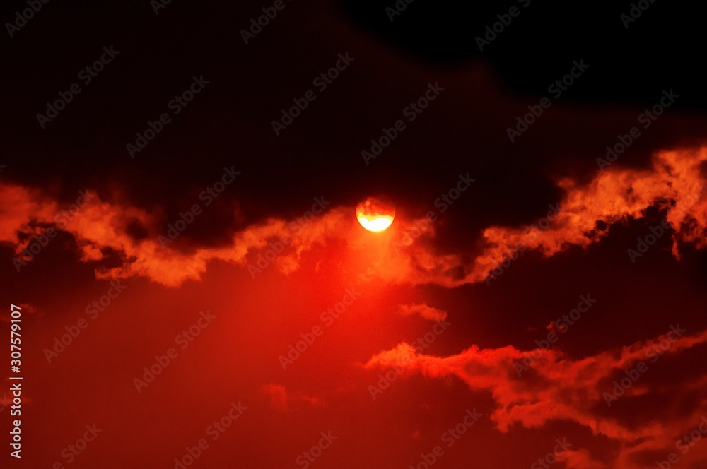 Fototapeta Breathtaking view of the sun setting in the beautiful cloudy red sky