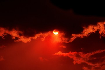Breathtaking view of the sun setting in the beautiful cloudy red sky