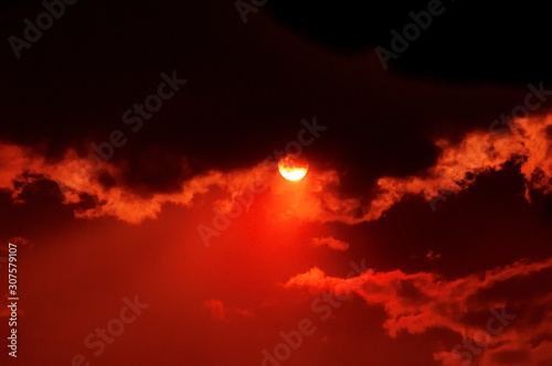 Foto op Plexiglas Rood traf. Breathtaking view of the sun setting in the beautiful cloudy red sky