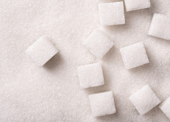 Loose granulated sugar and cubes close-up. Sugar background top view.