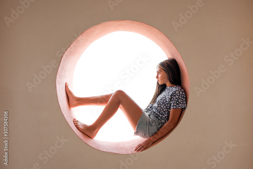Photo Young barefoot girl curled inside a round opening