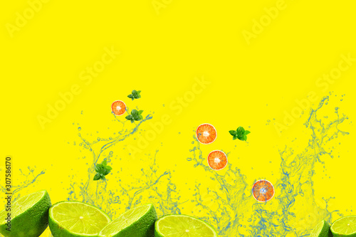Fototapeta water splashes and slices of orange and lime with mint on a yellow background obraz na płótnie