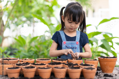 Adorable 4 years old asian little girl is fill the seeds to the pots for planting the vegetable in the garden outside the house, concept of kid learning activity at home Canvas Print