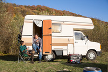 Man Sitting On The Stairs Of His Retro Camper Van In The Mountains