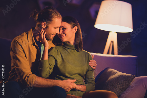 Close-up portrait of his he her she nice attractive lovely affectionate tender lovable cheerful dreamy couple girl sitting on divan spending day weekend kissing at night dark home house apartment