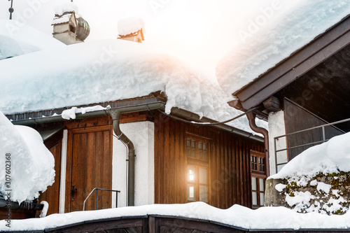 Roof of ancient wooden building covered with thick snow drift layer after heavy snowfall blizzard on street old european austrian Kufstein town Wallpaper Mural