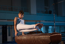 Little Male Gymnast Training In Gym, Flexible And Active. Caucasian Fit Little Boy, Athlete In White Sportswear Practicing In Exercises For Strength, Balance. Movement, Action, Motion, Dynamic Concept