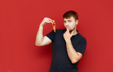 Portrait Of Cheerful Bearded Man With Tasty Slice Of Pizza In Hands On Red Background, Looks Into Camera, Smiles And Licks Finger. Man Enjoys A Delicious Pizza, Eats The Last Piece.