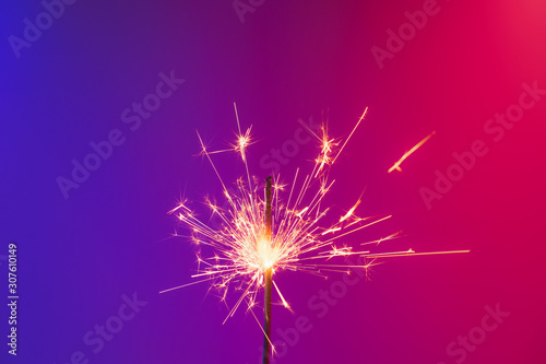 A burning sparkler in bright neon background. Concept of new year party or celebration: a bengal fire in vivid neon lights - 307610149