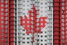 Canada Flag Depicted In Paint Colors On Multi-storey Residental Building Under Construction. Textured Banner On Brick Wall Background