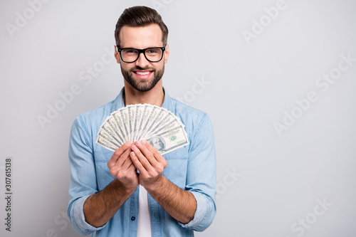 Fototapeta Photo of attractive handsome guy holding fan of american money dollars successful freelancer rich person wear specs casual denim outfit isolated grey color background obraz