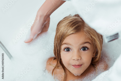 overhead view of happy kid taking bath and looking at camera near mother Poster Mural XXL
