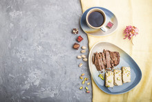 Traditional Arabic Sweets Sesame Halva With Chocolate And Pistachio And A Cup Of Coffee On A Gray Concrete Background. Top View, Copy Space.