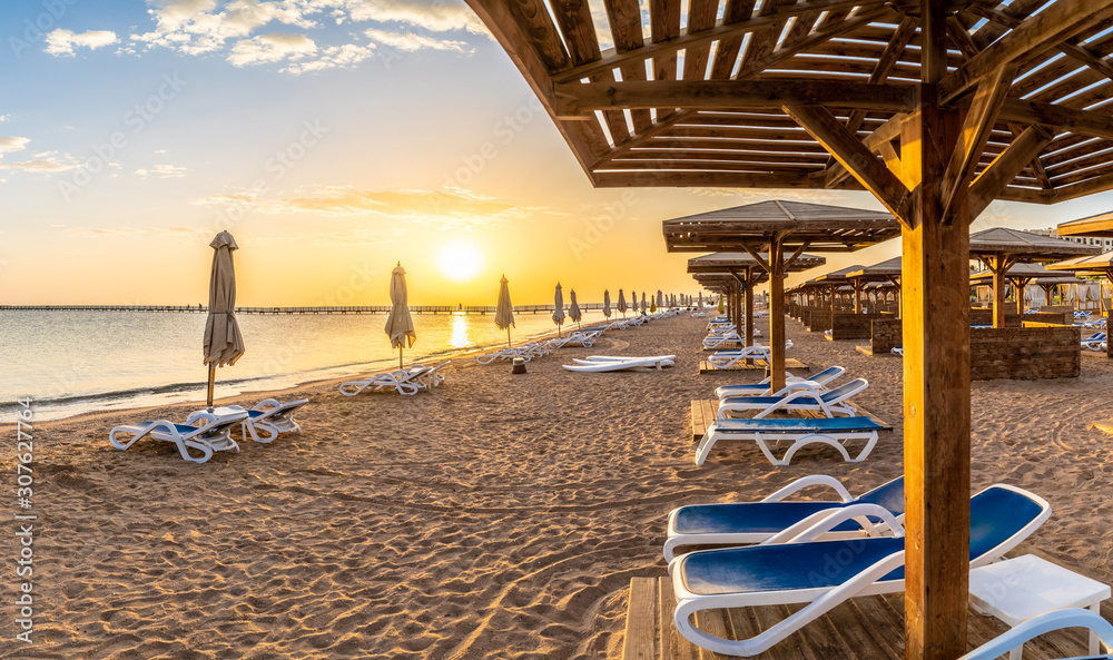 Fototapeta Landscape with sunbeds and umbrella on the Red Sea beach at sunrise in Hurghada, Egypt