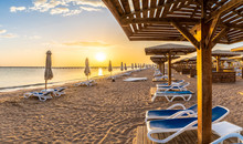 Landscape With Sunbeds And Umbrella On The Red Sea Beach At Sunrise In Hurghada, Egypt