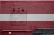 Latvia Flag Depicted On Side Part Of Military Armored Truck Closeup. Army Forces Conceptual Background