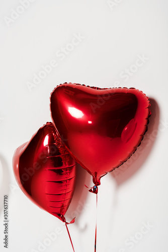 red and shiny heart shaped balloons on white
