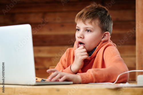 Shocked child boy with open mouth and bulging eyes looks at a computer laptop screen. Internet porn censorship concept, adult content 18+