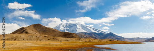 Panorama of the snow-capped Muztagh Ata mountain with Lake Karakul in the foreground Canvas Print