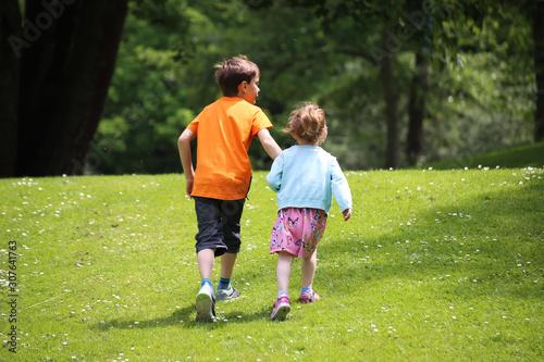 Junge und Mädchen (Geschwister) laufen auf einer Wiese Fototapet