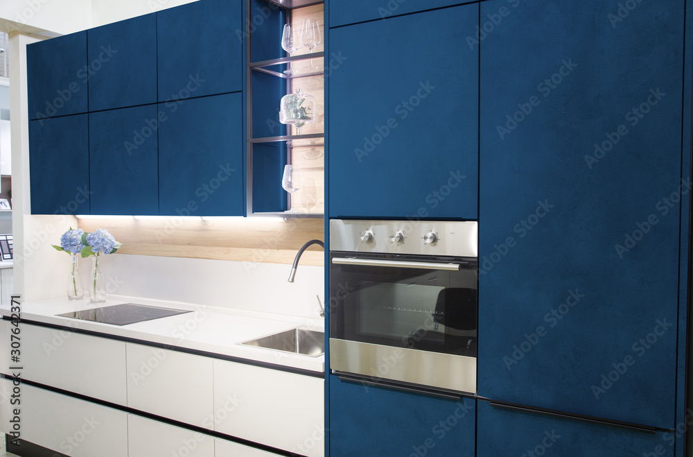 Fototapeta Modern kitchen interior with white brick walls, wooden countertops with a built in sink and a cooker.