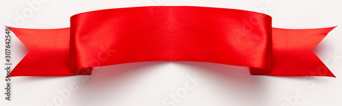 Fotografiet panoramic shot of red and satin ribbon on white