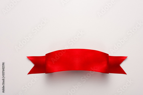 top view of red and satin ribbon on white