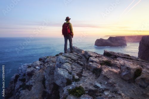 Obraz na plátne A rear view of of a lone male backpacker or hiker standing on a cliff top with a