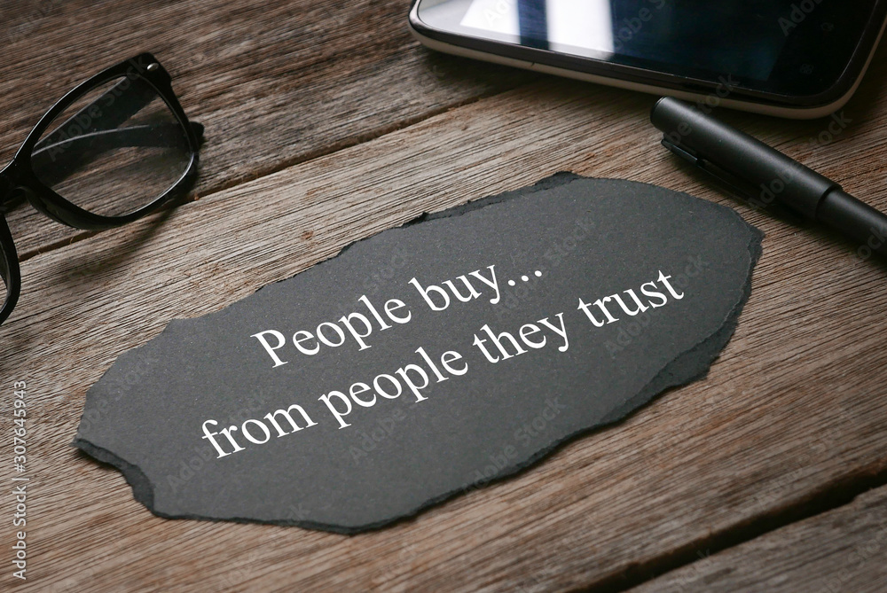 Fototapeta Glasses,mobile phone,pen,a a piece of black paper written with People buy...from people they trust on wooden background.