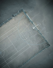 An Empty Gritty Cold Urban Inner City Basketball Court, Photographed From Above. Drone Photography Showing Court Lines, Tennis Court And A Concrete Basketball Court. Atmospheric Overhead Viewpoint.