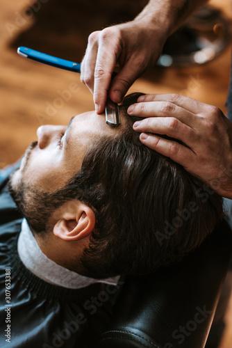 Fotografie, Obraz selective focus of barber holding sharp razor while doing haircut to man