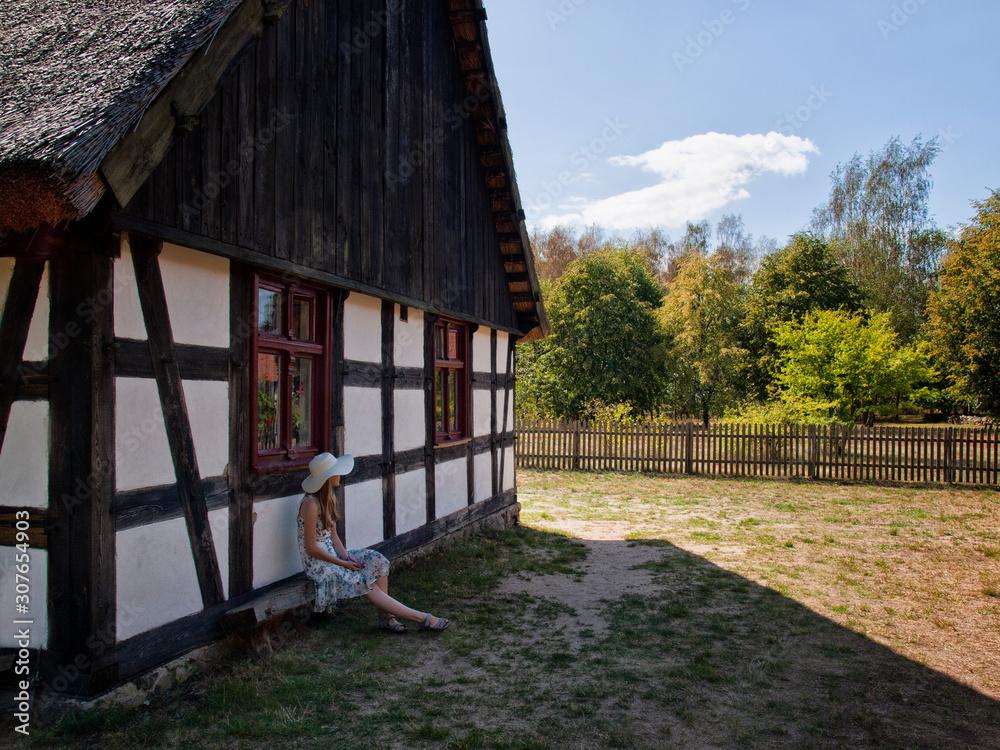 Fototapeta Sielskie życie na wsi. Zabytkowy dom o konstrukcji szachulcowej i kobieta w kapeluszu przed nim