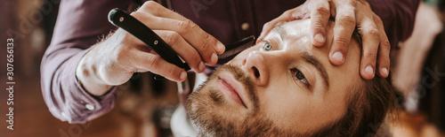panoramic shot of barber shaving bearded man