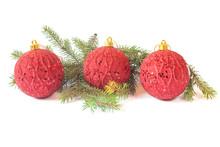 Three Red Baubles And Pine Branches Isolated On White Background
