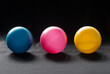 canvas print picture - Cyan magenta yellow plastic balls with black fabric background