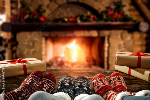 La pose en embrasure Amsterdam Desk of free space and people legs with christmas socks.Home interior with fireplace and