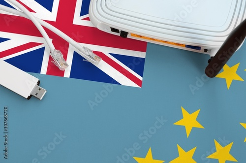 Tuvalu flag depicted on table with internet rj45 cable, wireless usb wifi adapter and router Wallpaper Mural