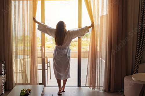Cuadros en Lienzo Young woman wearing white bathrobe opening curtains in luxury hotel room