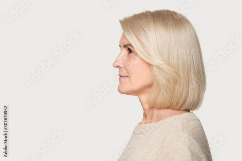 Mature woman profile view studio portrait isolated on gray background - fototapety na wymiar