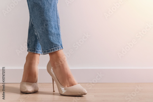 Woman's legs wearin jeans and high heel shoes standing onthe floor near the whit Obraz na płótnie