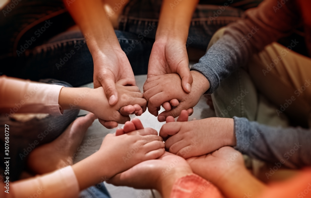Fototapeta In selective focus of adult and children hands holding together,collaborator,union,joining teamwork concepts,with love and care